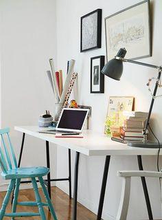 Una tabla blanca y dos taburetes de metal dan forma a este moderno y sencillo escritorio que apuesta ala sobriedad. Sólo tres cuadros que apenas tienen como común denominador el marco negro, un color que se repite en las patas del escritorio y en la lámpara. Para romper con la paleta de blancos y negros, se eligió una silla antigua que fue pintada de un llamativo turquesa.