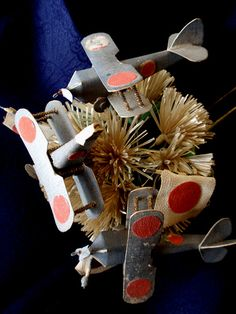 """Geiko-san & Maiko-san """"This is a Hana-kanzashi (Flower Hairpin) made for a Maiko (Apprentice Geisha) during the late 1930s. It is decorated with Matsu (Pine), Rising Sun flags, and Military Biplanes. The dark-grey colour of the aircraft suggests that they are intended to represent Naval Carrier Fighters."""" (source)"""