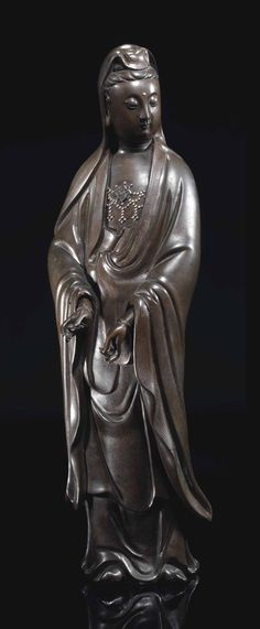 A LARGE SILVER-INLAID BRONZE FIGURE OF GUANYIN - CHINA, QING DYNASTY, 18TH CENTURY.