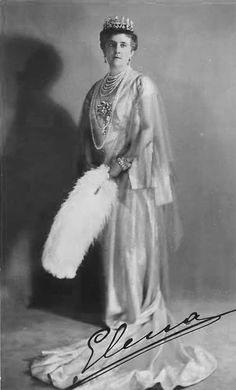 Queen Elena of Italy wears a simple post World War I dress with matching jacket and carries a theatrical fan in this photo