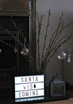 Not on the high street : Monochrome Christmas Decorations - Cinema light box on a hearth. Santa is coming with a twig display in a vase.