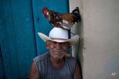 Jose poses with his rooster named Luis to be photographed for tourists in Trinidad, Cuba, Sunday, Oct. 11, 2015. (AP Photo/Ramon Espinosa)