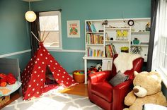 I love this room!  Making your grandparent's home your own: Fit for a boy, this blue and red room is bright and cheery. Baby Marcus has his own tent, a comfy red leather chair and a gray wooden toddler bed here.