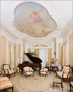 Living room with grand piano.  I love all the small chairs.