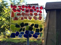 Fused glass rainbow colored garden stake. The glass has been hand cut and fused in my kiln. The glass is attached to a threaded rod with a
