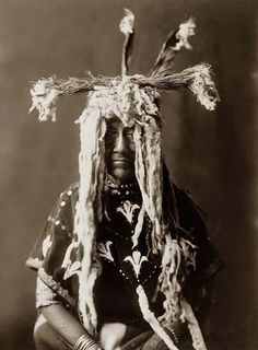 You are viewing an impressive image of a Sacred Indian Head-dress. It was taken in 1910 by Edward S. Curtis.    The image shows Piegan man, half-length portrait, seated, facing front, wearing headdress made of ermine tails, feathers, and bunches of grass.    We have created this collection of pictures primarily to serve as an easy to access educational tool. Contact curator@old-picture.com.