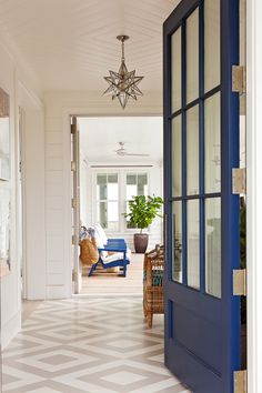 This coastal entry features a blue front door and painted wood floors. Star pendant is from Vaughn Lighting.