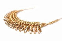 A Gold Necklace, a ChampakaliA  A flat wide collar, decorated with strung, stylised buds of the fragrant jasmine flower, executed in gold and embellished with stamped units, granulation and small gold balls.  India, Maharastra, early 20th century