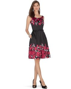 From White House Black Market:  Sleek and structured fit and flare satin dress blooms with beauty from the neckline and hem with red rose prints. Stylist Note: Complete this classically feminine look when paired with strings of pearls and embellished minaudere.