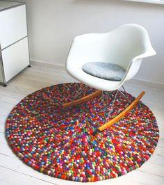 DIY-Teppich aus bunten Filzkugeln. Einfach die Kugeln aufreihen, zu einer großen Schnecke legen und an der Unterseite vernähen.