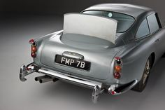 The original 1964 Aston Martin James Bond car features a retractable bullet-proof screen, oil slick ejector from left-side tail light, nail ejector from right-side tail light and a smoke screen pipe next to the exhaust. Aston Martin Db5, James Bond Cars, James Bond Movies, Jaguar, Cool Old Cars, Nice Cars, Car Gadgets, Motor Car, Cars