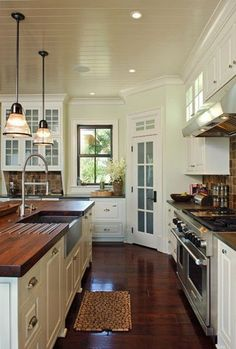 Bead board ceiling and dark hardwood in kitchen, White cabinets with butcher block countertops & the sink!