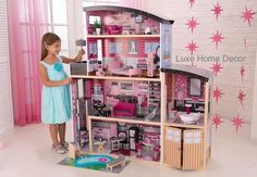 """Over 4 ft tall and over 4 ft wide, there are so many goodies packed into the glam house! This wooden dollhouse is any young girl's dream. 30 pieces of fabulous, modern furniture included. Dolls can take a ride from the first floor to the second on the gliding elevator. The backyard area is complete with a bbq grill and swimming pool. Spiral staircase, outdoor patio area. Two doors that open and close. Fits dolls up to 12"""" Dimensions: 49.4"""" L x 25.7"""" W x 53.3"""" H"""