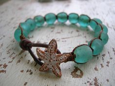 Handmade recycled glass orbs glow like glistening bits of sea glass on this beachy hand-knotted bracelet. Strung on distressed leather and whimsically knotted with sturdy cord, the soothing colors and worn texture evoke memories of salty breezes and foaming surf...  This listing is for one single Beachcomber bracelet in sea blue/green. **Please note that these beads are made by hand and that the colors may vary ever so slightly!**  Also available with a nautilus shell button - specify yo...