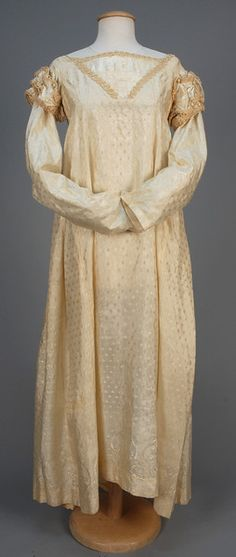 AMERICAN REGENCY SILK GOWN, c. 1815. - Cream figured silk having empire bodice with tucked insert and long sleeve trimmed with satin ribbon, silk cord and buttons, skirt patterned at the hem with floral clusters and swags, muslin bodice lining and hem backing. whitakerauction