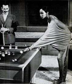 """Iconoclastic model Donyale Luna shoots pool with the legendary Groucho Marx in a scene from the film Skidoo in 1968. In the film, directed by Otto Preminger, Mr. Marx played """"God"""" and Ms. Luna played his mistress. It's a long story."""