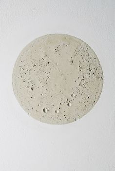 """Mamiko Otsubo - """"Concrete Moon"""", 2010, cast concrete embedded into drywall, 6.5"""" in diameter"""