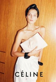 Daria Werbowy wears a clutch with knotted clasp with black knotted bracelets and headband.