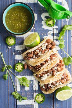 Pinto bean tacos with salsa verde made with beans, onion, garlic, tomatillos, jalapeño and queso fresco. Recipe via greenhealthycooking.com