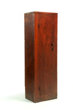 """SHAKER DIMINUTIVE CUPBOARD -    Canaan, New York, 19th century, pine and butternut. Originally a built-in, small and narrow size with interior shelves, a one-board door, and old red paint. 49""""h. 15.5""""w. 11.5""""d. Purchased from a house across the road from the Canaan Shaker settlement."""