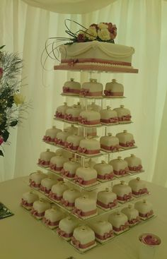 Mini Wedding Cakes for the personal gift to your guests.  50 Mini Wedding Cakes on an Acrylic tower stand with a top cake for cutting.  More about mini cakes at http://www.annescakecreations.co.uk/mini_cakes.html