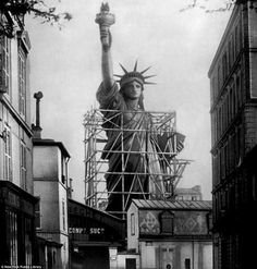 The Statue of Liberty surrounded by scaffolding as workers apply finishing touches in Paris (1885).