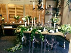 Wedding Layout at the Spier Winelands Bridal Fair I Table Runner with foliage and airplants with a variety of bridal bouquets and button holes. The chair tie backs are made from Ruscus. This makes a gorgeous centerpiece