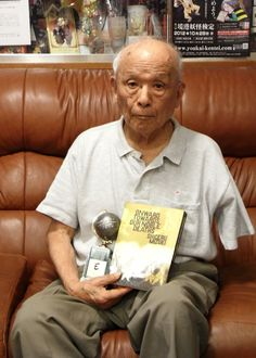 Shigeru Mizuki posing with his recent Eisner Award for his book Onward Towards Our Noble Deaths.