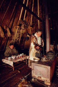 Inside a reindeer skin tent a Nenets woman makes tea on a stove. Yamal. Siberia. Russia.