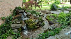 We built this Pondless Waterfall in this outdoor patio spot over 12 years ago and it's still going strong. Stone patios and a gas fire pit complete this outdoor lifestyle area.