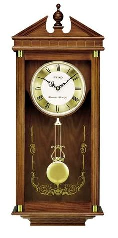 "Chiming, dark brown solid oak traditional wall clock. Curved Glass Crystal with spun brass moving ""Lyre Style"" pendulum. Reeded columns grace each side of the clock with brass accents at the end of each column. Westminster/Whittington hour only chime , hourly strikes, volume control and nighttime silence option.   Size: H 28 1/4"" W 11 1/2"" D 4 3/4"""