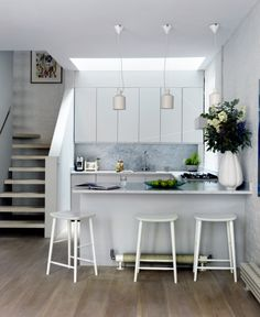 Small but perfectly formed, this compact contemporary kitchen keeps things simple with whitewashed walls, handleless cabinetry and minimalist décor.