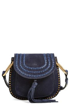 A swishy tassel, brassy studs and dense decorative topstitching add '70s-inspired flair to this structured shoulder bag.
