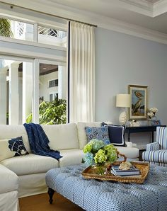 Living room: white sofas, big ottoman, pale blue walls with wide white molding, blue and white print accents.