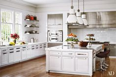 The family-friend chef's kitchen is pristine with over-scaled subway tile, optic white glass slab countertops and contemporary cabinetry. Reclaimed oak floors and Czech factory lighting by Ann Morris Antiques soften the look.