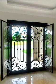 Mirá imágenes de diseños de Puertas y ventanas de estilo clásico en negro: Puerta de entrada de hierro forjado. Encontrá las mejores fotos para inspirarte y creá tu hogar perfecto.