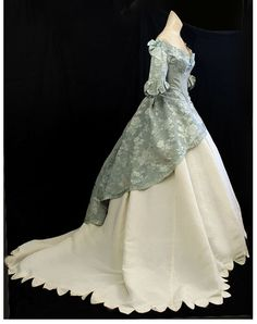 Unusual ball gown ~ Ivory silk bell skirt with scalloped hemline with a sweep train.  Pale aqua print silk bodice spills into an overskirt - short in the front falling in length down the back.  Scoop neck with ruffled trim with bows.  Sleeves end at the elbow with a bow.