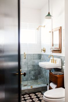 Small, tiled bathroom with small mirror and light fixture