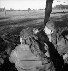 Sergeant H.A. Marshall (left) and Corporal S. Kormendy, both of The Calgary Highlanders, observing terrain from a concealed firing position during a scouting, stalking and sniping course, Capellen, Belgium, 6 October 1944.