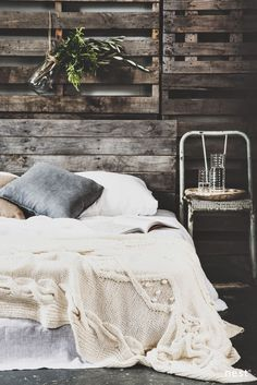 Love the reclaimed wood o the walls with the contrast of soft light colored bedding
