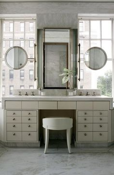 WHITE + GOLD: sinks and mirrors layered in front of windows.