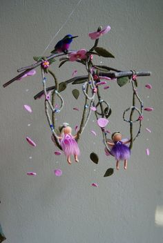 """This mobile is about 15"""" long and it has a diameter of approx. 14"""". The little fairies are about 3,5"""" and 4,0"""" high and each humming bird about 3"""". The fairies, the birds, the leaves and the flowers are made of pure sheep's wool. The fairy-wings are made of tissue paper. I have fastened them, with much patience, with nylon strings on a beech twig."""