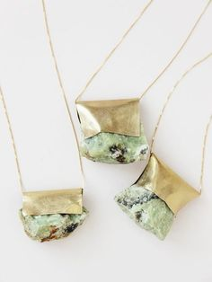 Beautiful folded gold sheets with a simple gold chain feature a gorgeous mint green stone