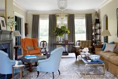 A pair of Napoleon III chairs and a 19th-century wing chair surround a custom horsehair-covered ottoman in the living room; the sofa, in a Clarence House fabric, cocktail table, and rug are custom designs, the lanterns are from Ann-Morris, Inc., and the curtains are in a Claremont silk.