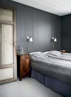 grey panelled bedroom, grey bedding and wood side cabinet
