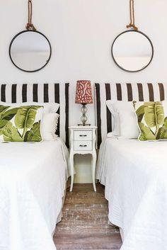 Estilo aireado, playero y elegante en la ciudad: cuarto de dos camas individuales en blanco, negro y verde, con detalle de almohadón estampado con hojas de banano y espejos circulares.