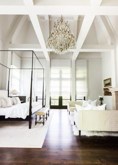 Light and airy bedroom with sky high ceilings, a canopy bed, and a crystal chandelier, designed by Chad James and photographed by Alyssa Rosenheck.