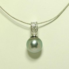 Enjoy the simplistic beauty of this Tahitian black pearl pendant. This pendant features a 13mm Tahitian black pearl set with Cubic zirconia gems in sterling silver.