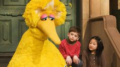 Big Bird, played by puppeteer Caroll Spinney, reads to Connor Scott and Tiffany Jiao during a taping of Sesame Street in 2008 in New York