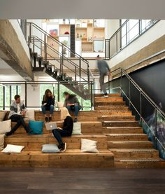 Collaborative Space >> Unique Office Design Ideas >> This broad timber staircase connects the two floors of London creative agency, Anomaly, exposing the raw edge of the concrete slab and new steel beams. The unfinished edges contrast to the smooth clean lines and tie in with the rough cut finishes of the staircase and balustrade. At the base of the stairs is an auditorium space comprising of textured bleacher seating clad in scaffold planks.